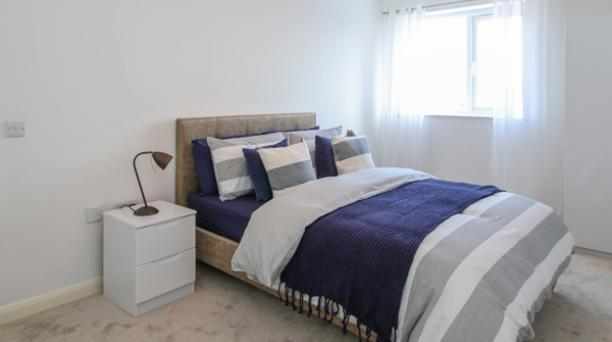 double bedroom with white walls and large window
