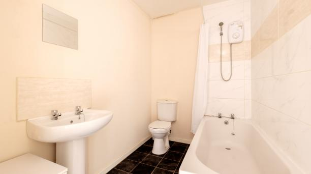 beige bathroom, bathtub and shower combined, toilet, wash basin
