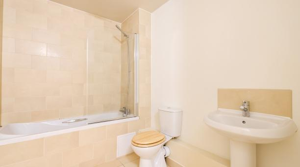bathroom inside buy to let property, beige tiles, bath tub, and white sink basin