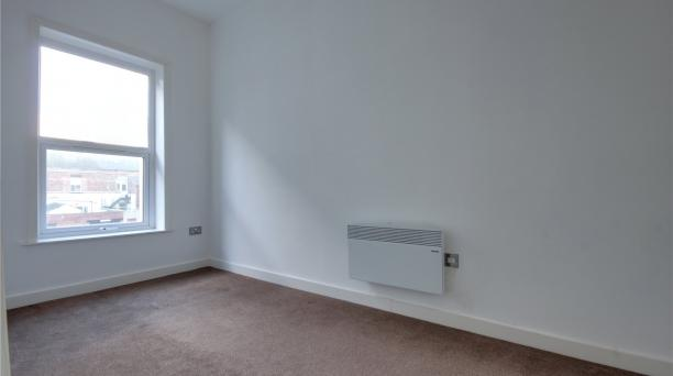 white walls, brown carpet, radiator