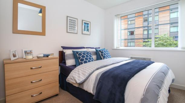 white bedroom, cream carpet, light oak furnishings, double bed, large window