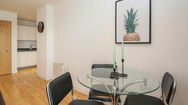 glass dining table, glass table, artwork of pineapple on wall, laminate floor