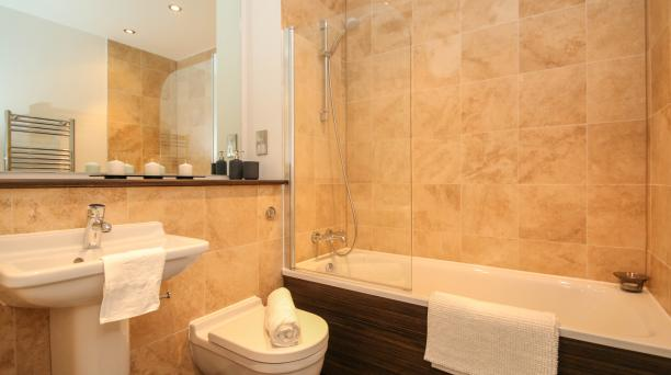 modern, beige tiled bathroom, bathtub, toilet, sink, large mirror