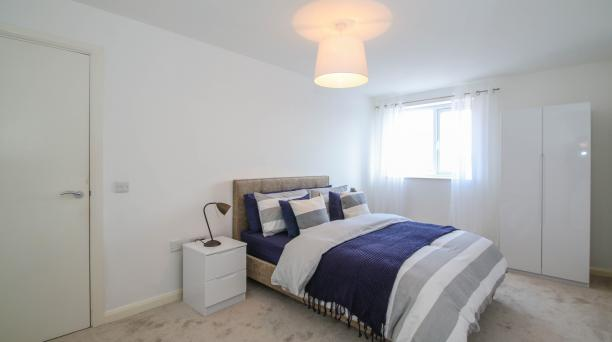 white bedroom in buy to let property investment large double bed and purple themed bedding and white bedside table
