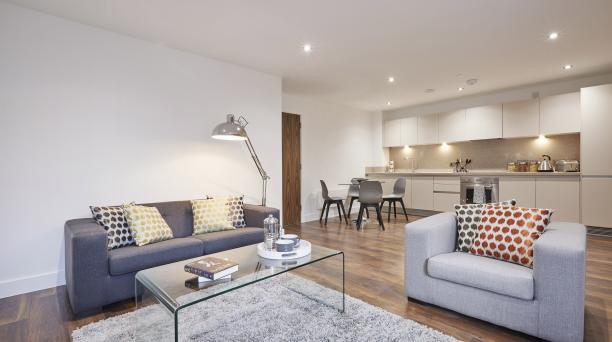 combined living room and kitchen in buy to let property, large dark grey sofa, two seater grey sofa centered around a glass coffee table on top of a grey rug and spotlighted ceilings and white themed kitchen.