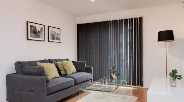 lounge area with dark blinds and dark grey sofa and glass table