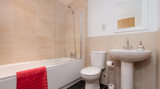 bathroom with beige tiles and white furnishings