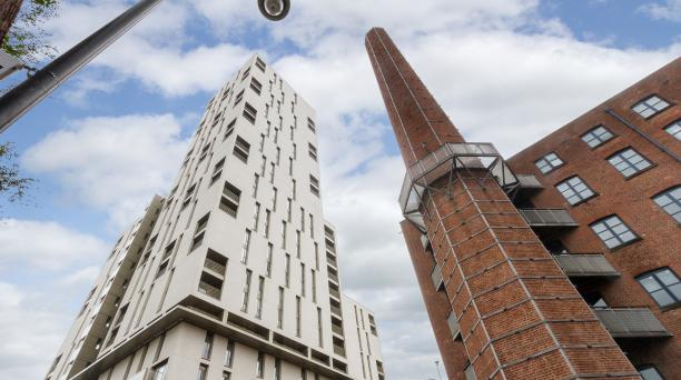 property investment in liverpool, large white skyscraper next to an old fashioned mill
