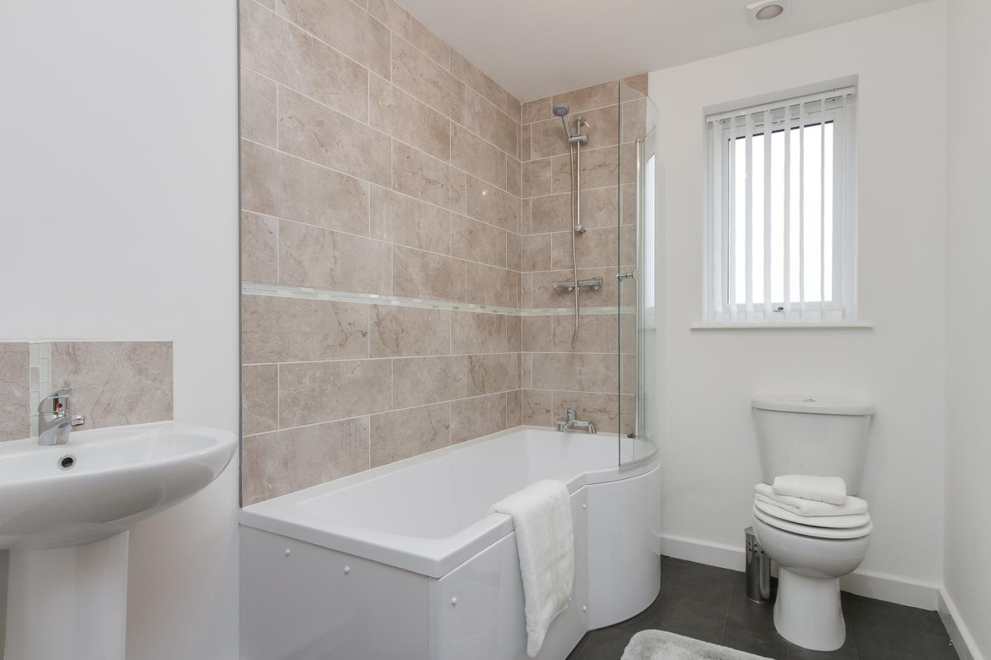 beige tile bathroom, white features