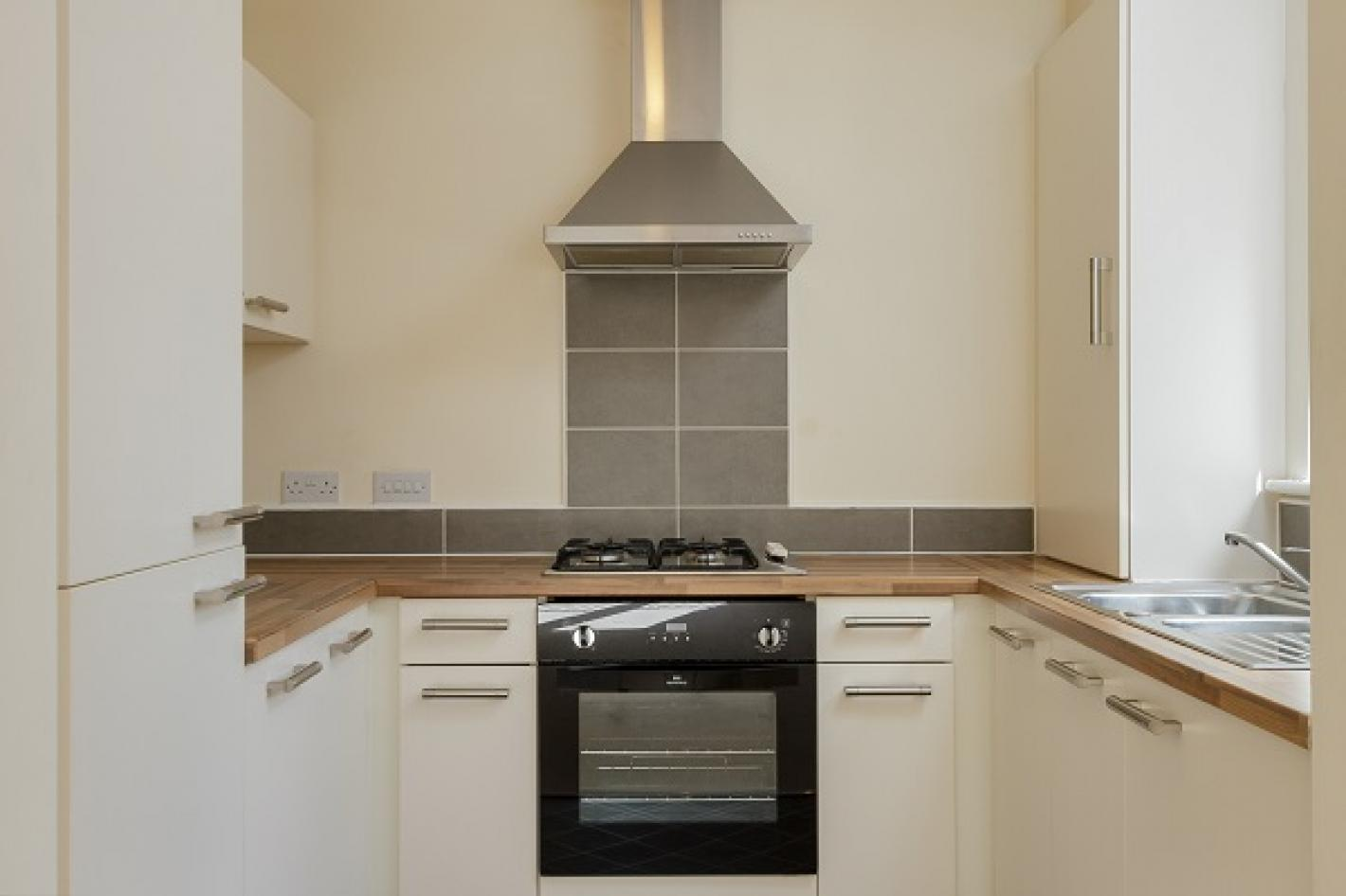 light grey tiled kitchen, white walls, white cupboards