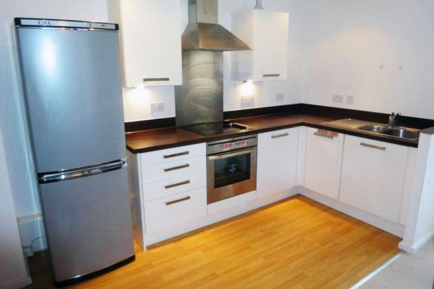 large kitchen with white cupboards, wooden floors and family size fridge