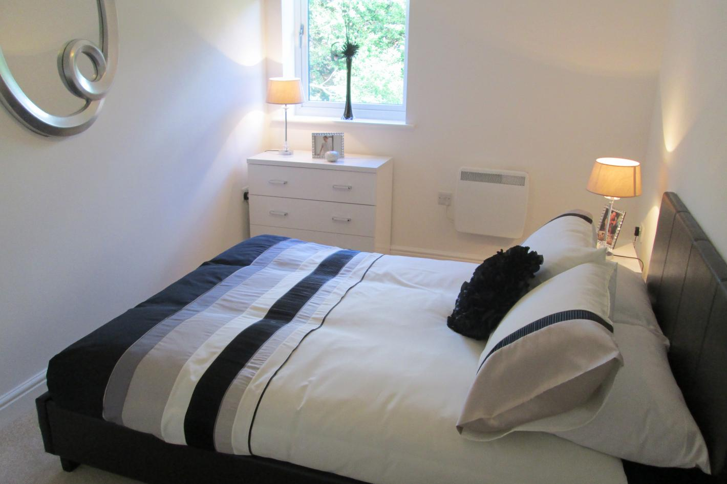 double bedroom, white and purple bedding, single window on wall
