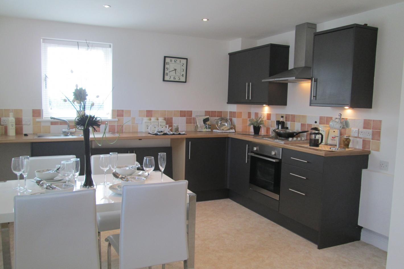 kitchen, dining area, glass table, white chairs, black cupboards, built in oven, white worktops, white walls