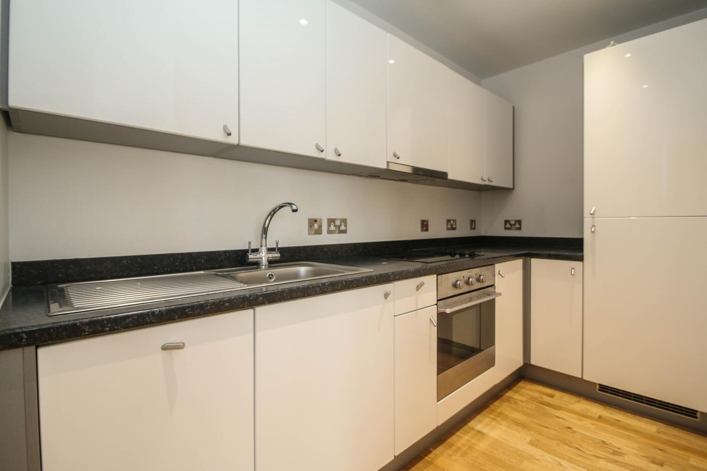 white kitchen, black worktops, built in oven, laminate flooring