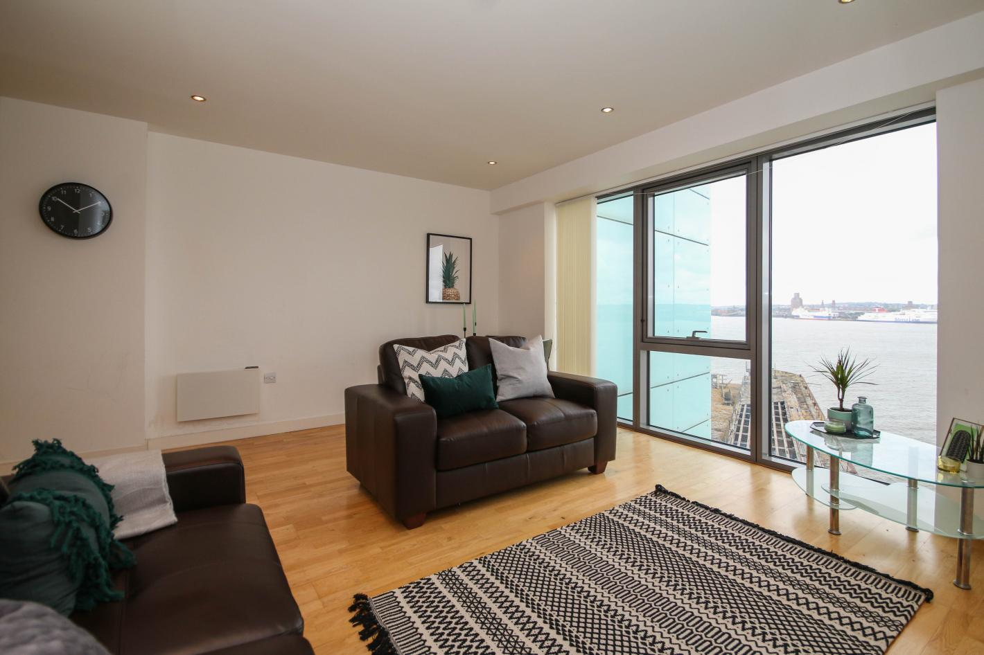 living room, triple window, 1 2 seater brown leather sofa, 1 3 seater brown leather sofa, laminate flooring