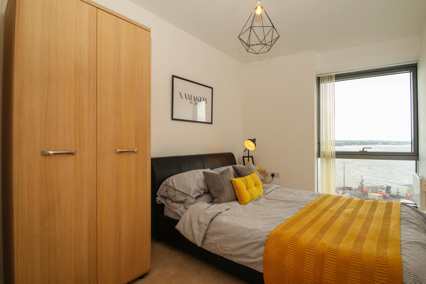 double bedroom, black double bed, white and yellow bedding, small wardrobe