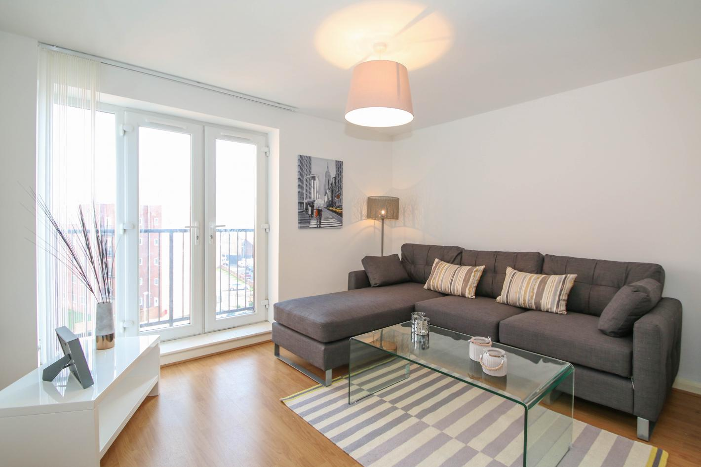 lounge in buy to let property deal, large grey corner sofa, laminate flooring, glass coffee table and white walls plus a large patio style window