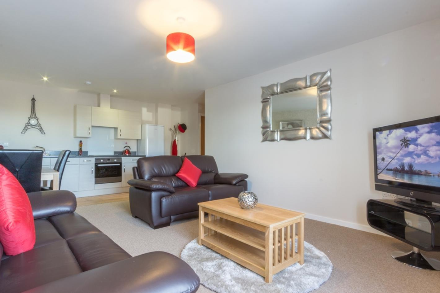 lounge and kitchen area, large sofas, white kitchen cupboards