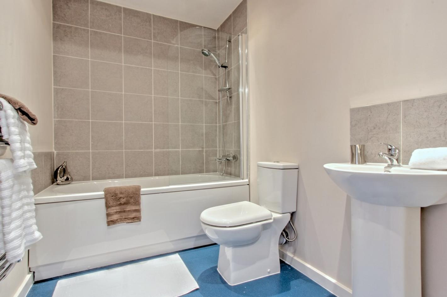 bathroom with blue flooring and beige tiles