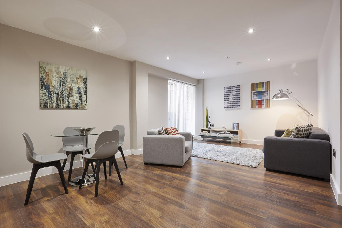 lounge and dining area in buy to let property, spotlighted room with single grey arm chair, dark grey double arm chair, dark wooden laminate flooring and glass dining table with grey chairs