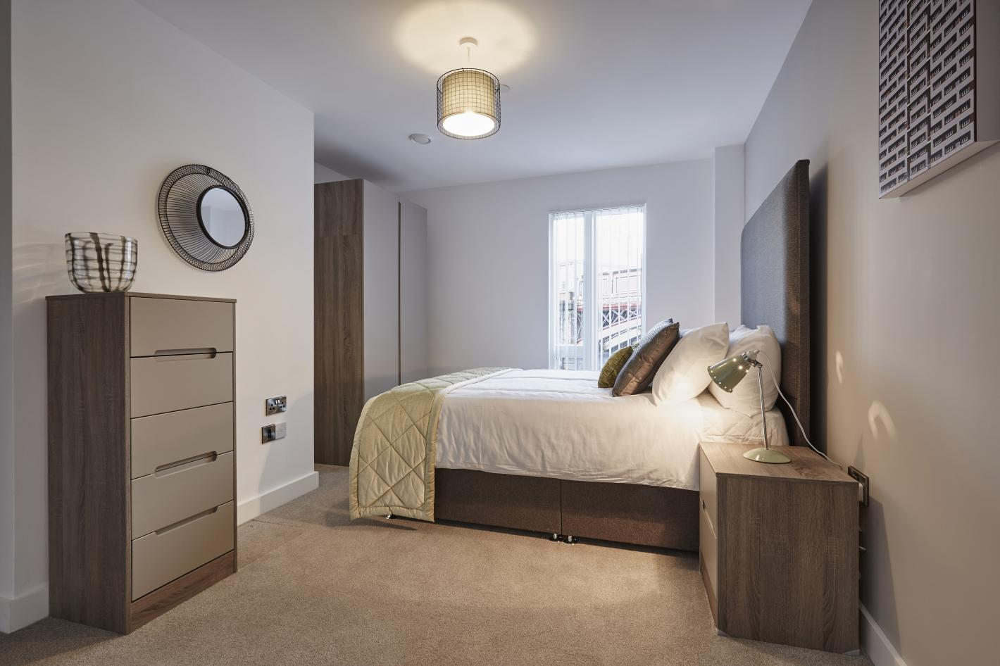 bedroom in buy to let investment, white walls, large double bed in the middle of the room, chest of draws to the left and bedside table