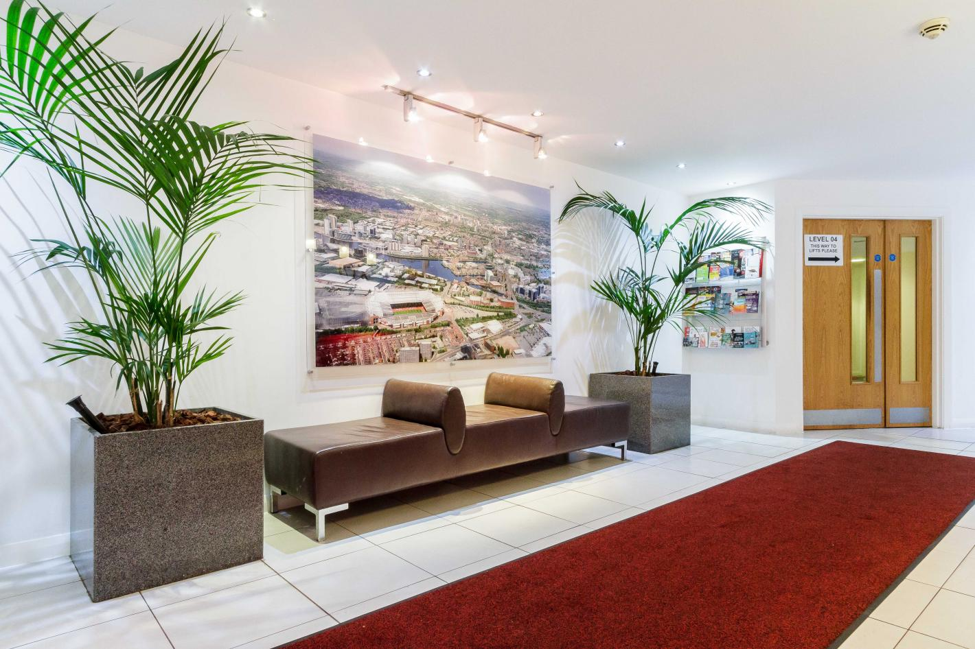 white lobby with red carpet and art work