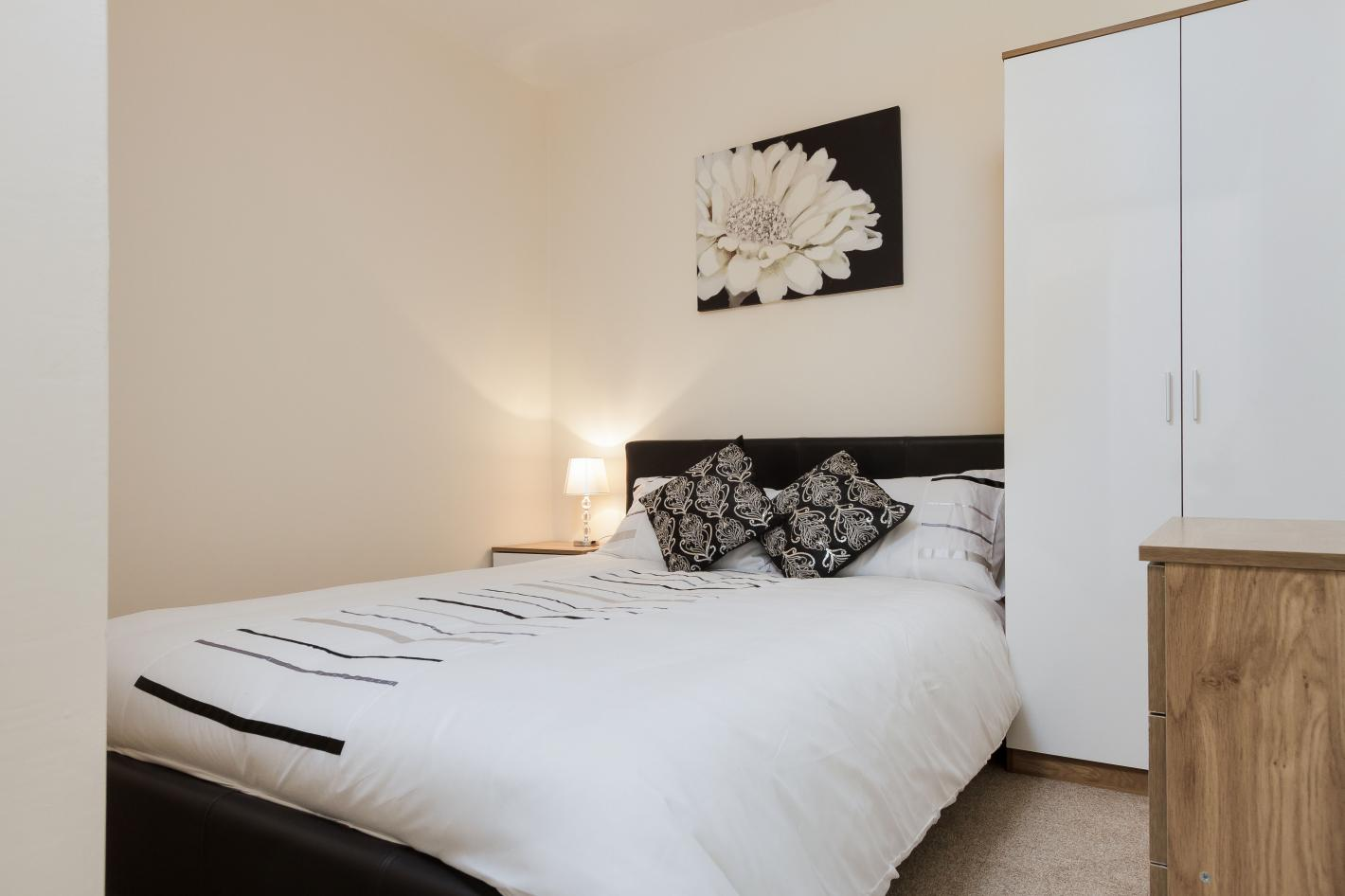 double bedroom, white bedding, black cushions and white wardrobe