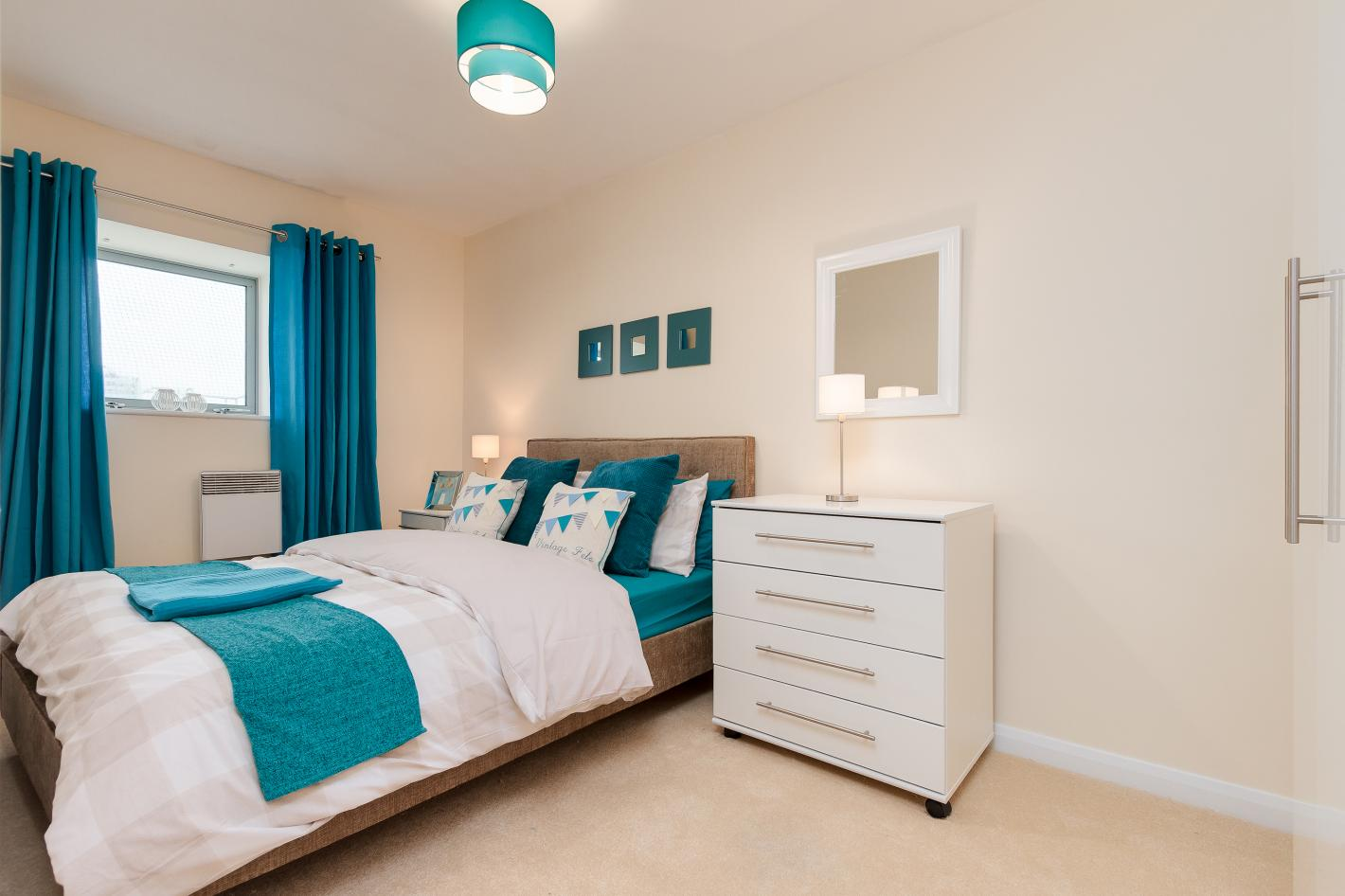 white bedroom with white chest of draws, white bedding and turquoise detailing