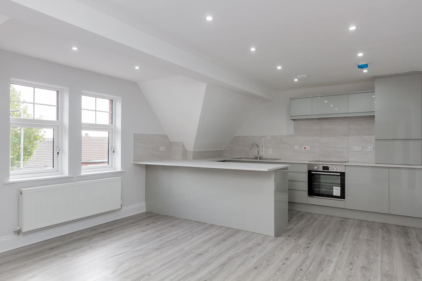 buy to let investment with modern style kitchen with white cabinets, white walls, grey laminate flooring, large breakfast bar in the middle of the room.