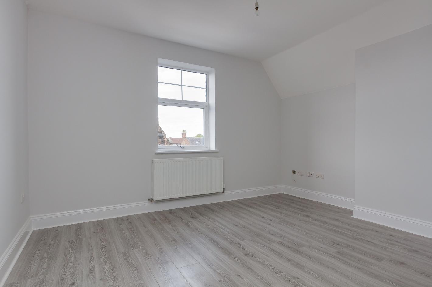 bedroom in buy to let property, white walls, single window on far wall and grey laminate flooring