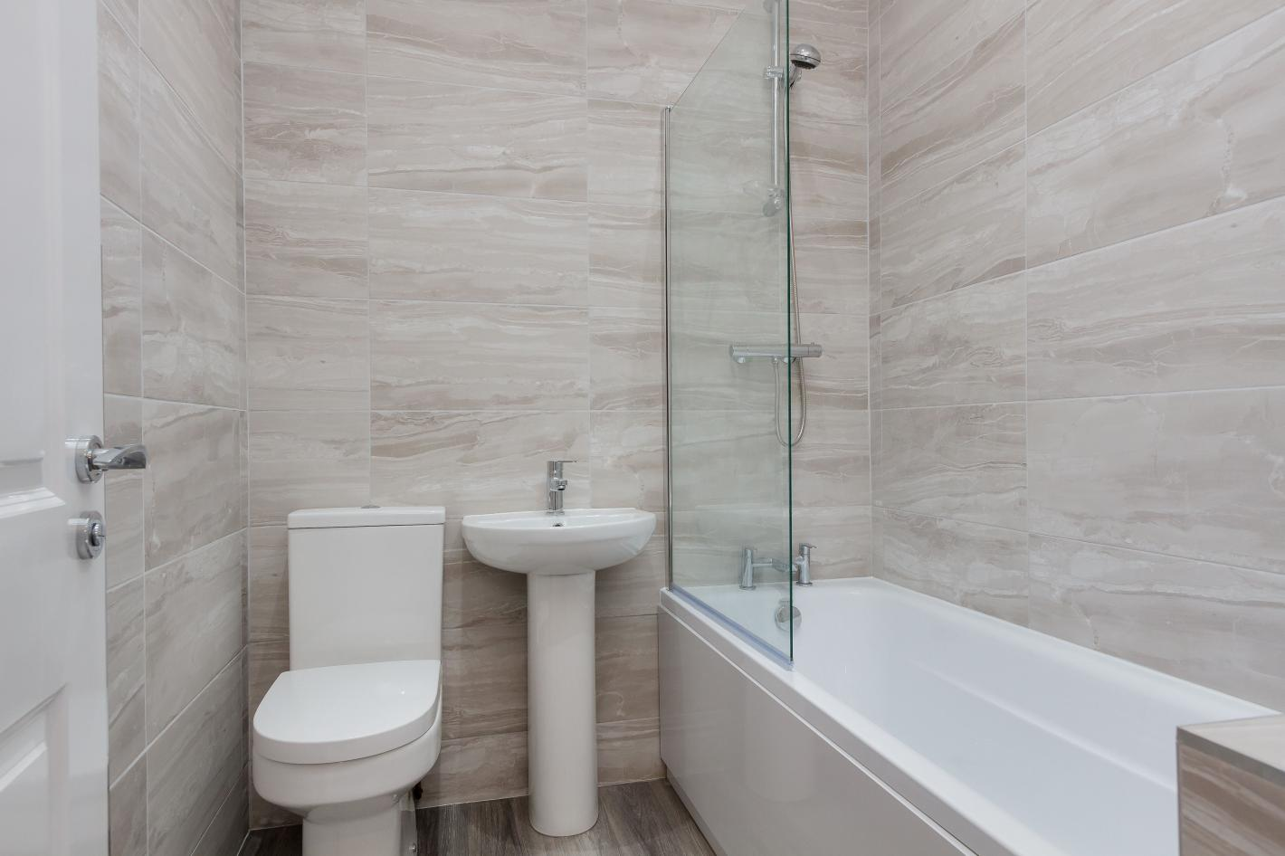 modern style bathroom, light grey tiles, white toilet, white sink with silver single tap, a white bathtub and shower combined