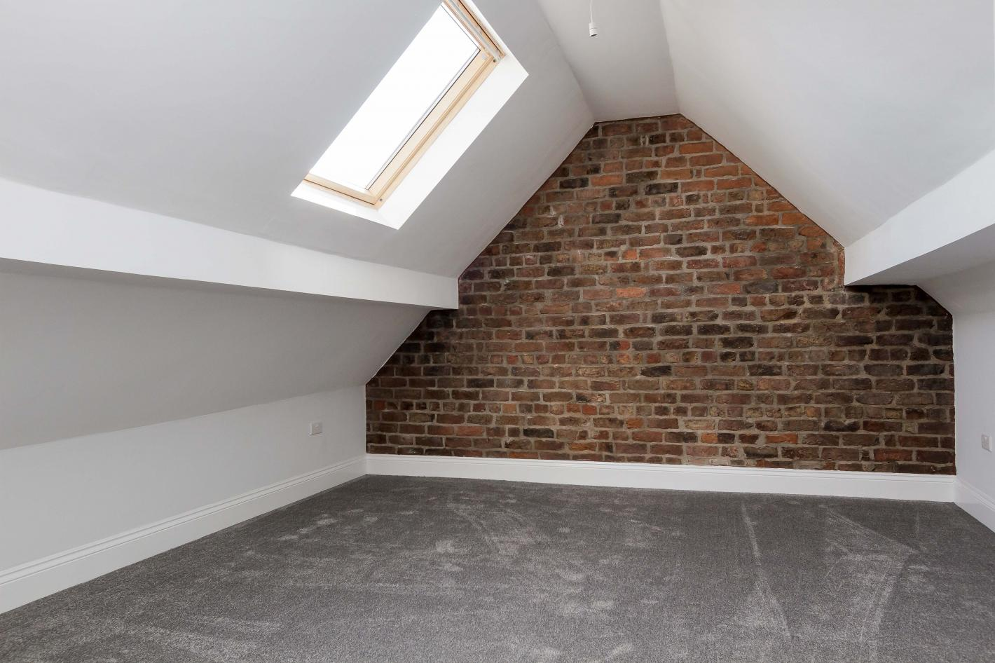 large bedroom in buy to let property. Attic style conversion with one brick wall, white walls and grey slate flooring