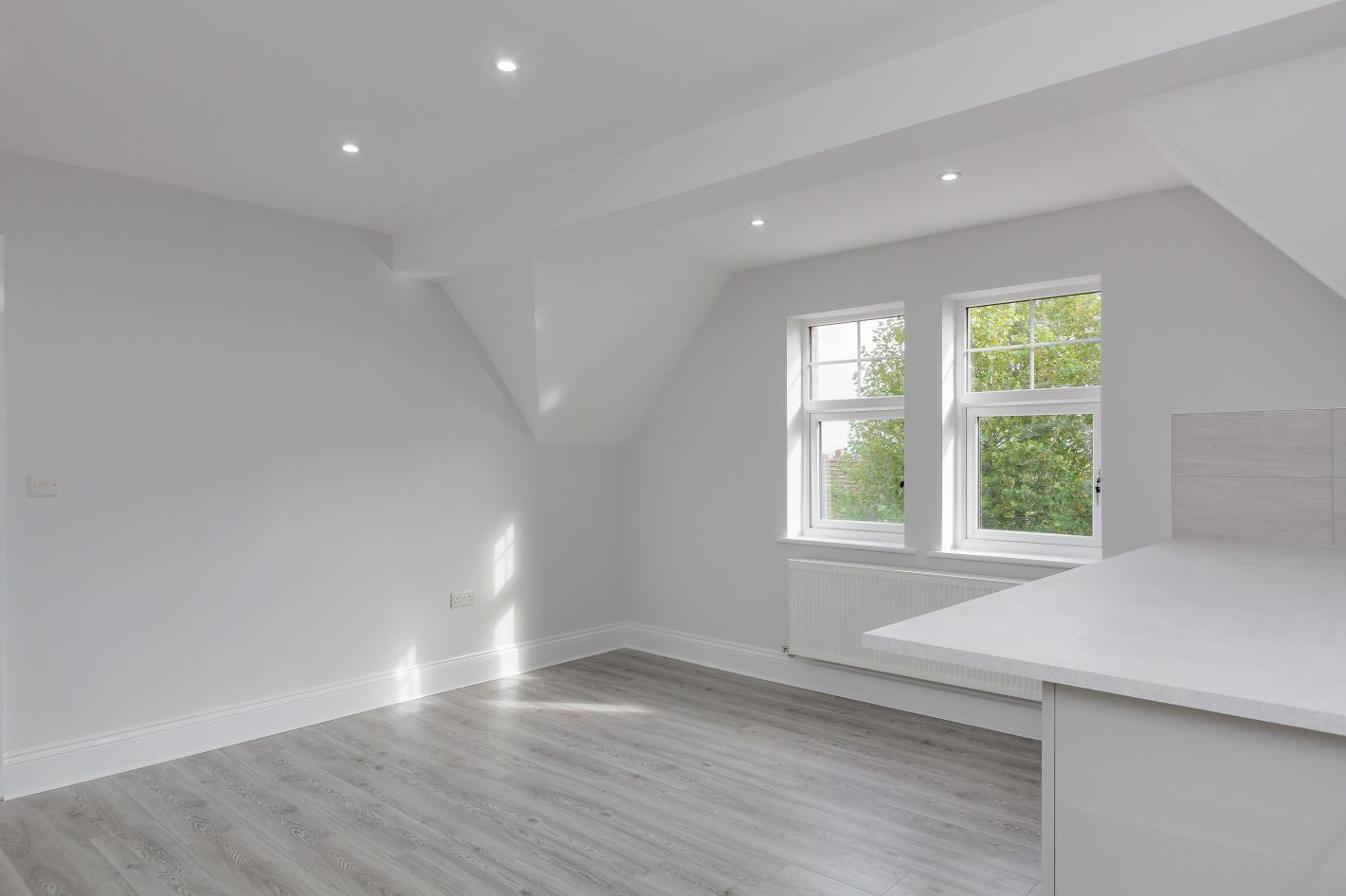 buy to let investment bedroom with white walls and grey laminate flooring, a large double window and spotlights on the ceiling.