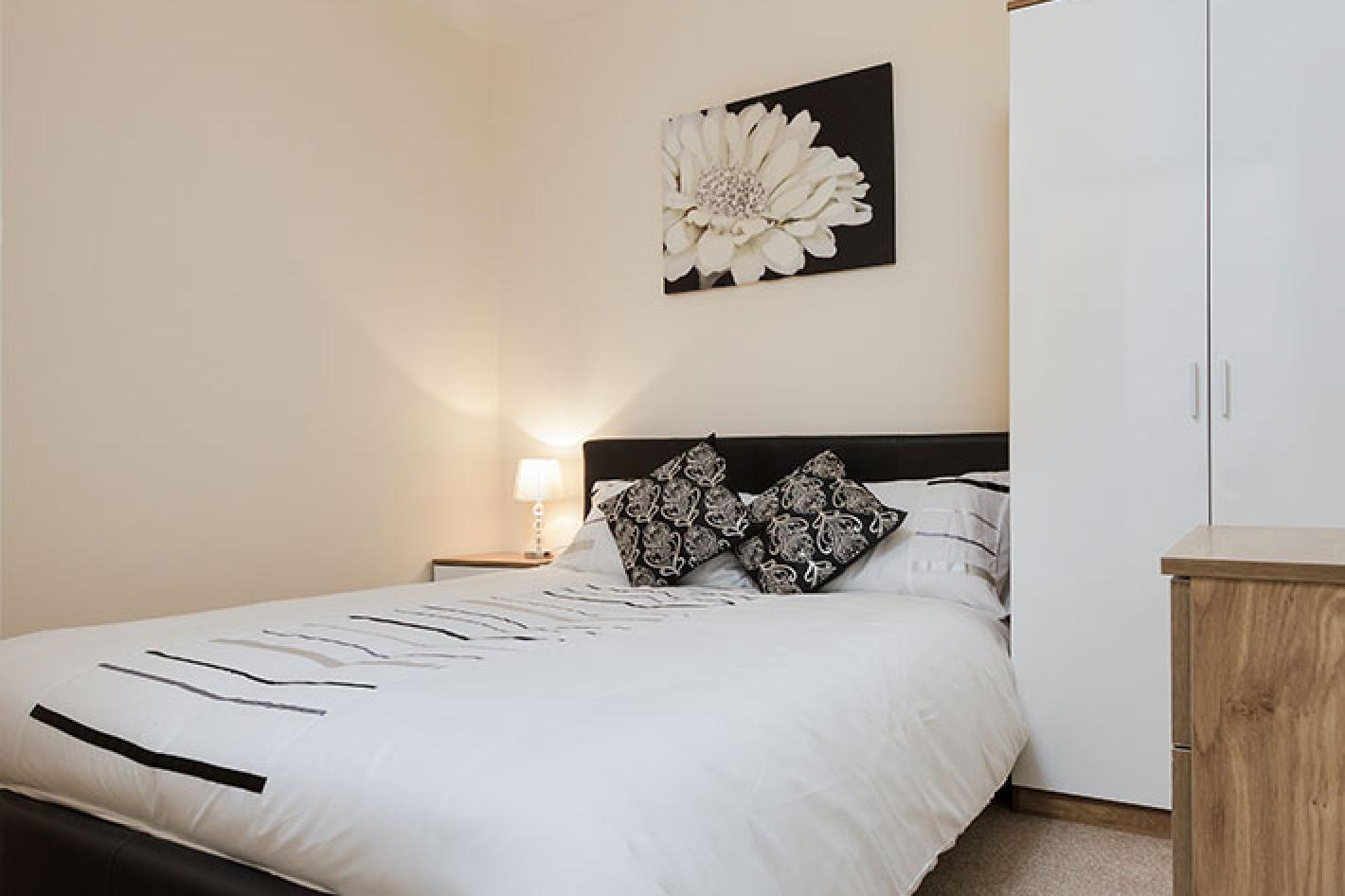 white bedroom with double bed that has a black bed frame and white and black artwork on the wall