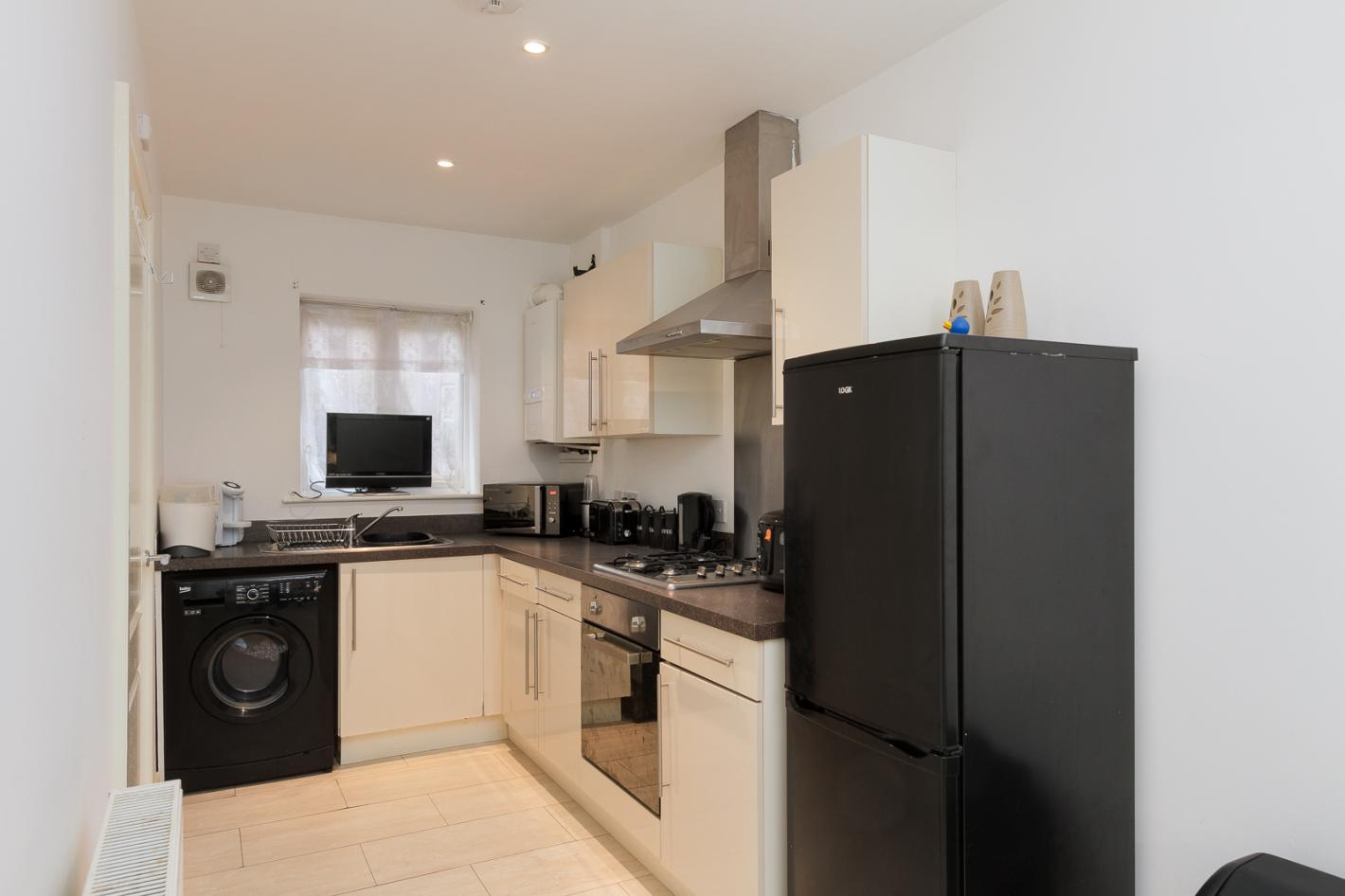 white kitchen, black worktops, spotlight ceiling