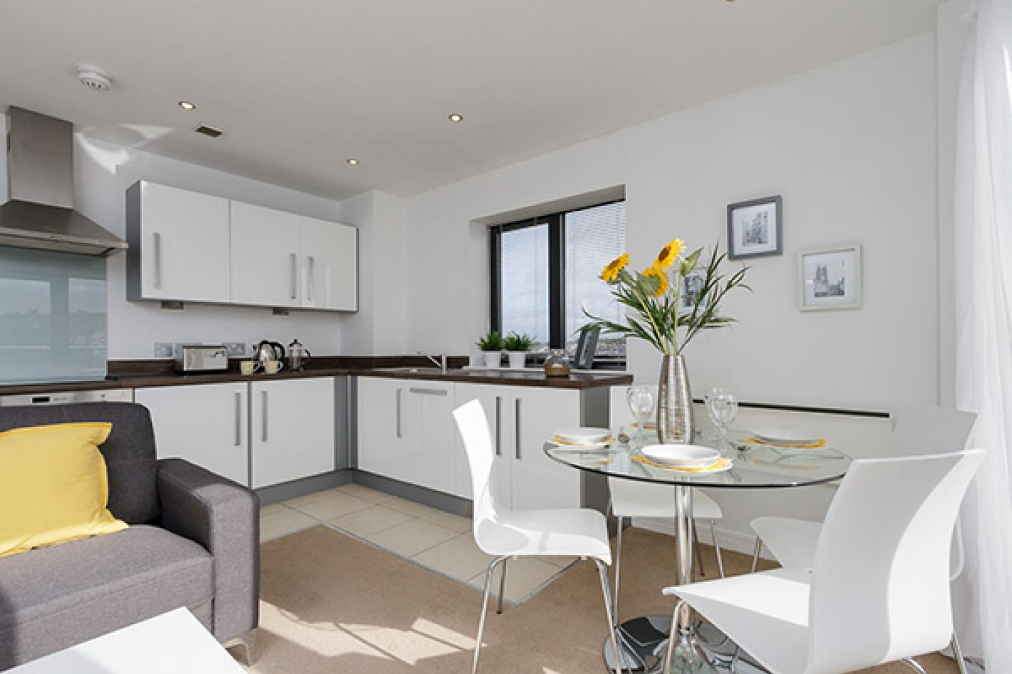 kitchen and dining area, white cupboards glass table and white chairs