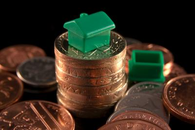stack of pound coins with toy green house on top