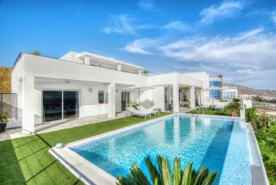 white villa with large swimming pool and greenery surrounding the pool