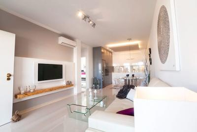 living room with dark walls, tv on wall and white sofas.