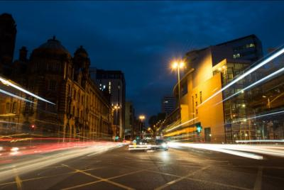 busy manchester steet at night lit by street lights